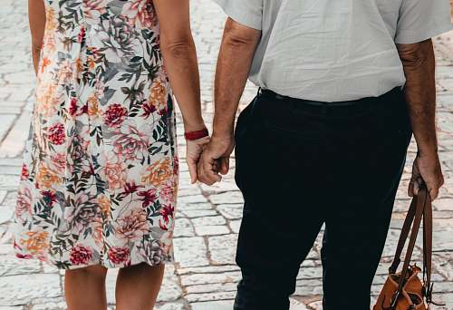 person man and woman holding hands close-up photography holding hands