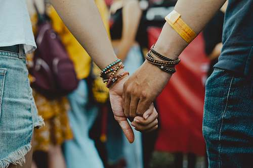 human man and woman holding hands near people person