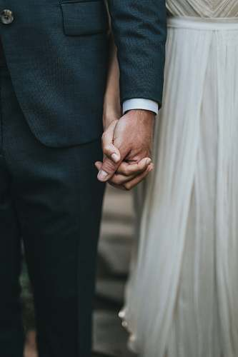 person man in suit holding hands with woman in white skirt human
