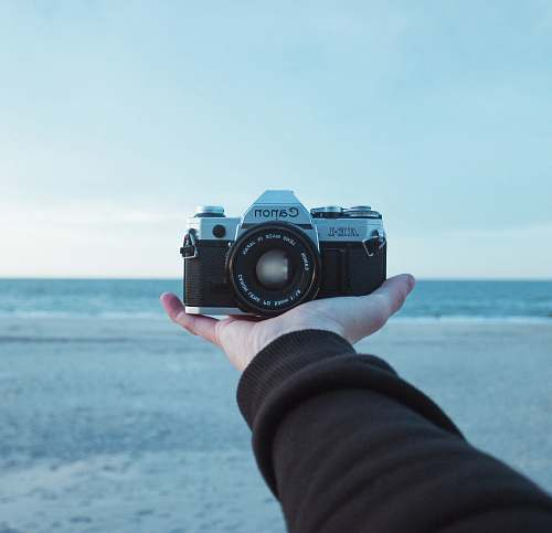 photo camera person holding black and gray Canon AE-1 bridge camera electronics free for commercial use images