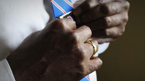 ring person holding blue necktie suit