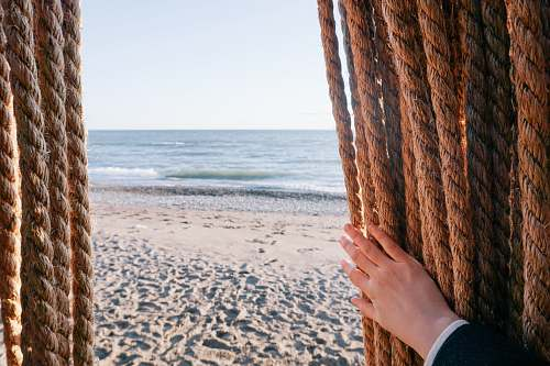 sea person holding brown rope over seeing body of water shore