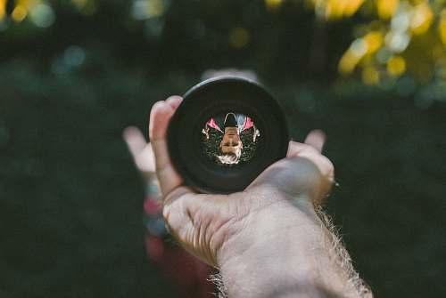reflection person holding camera lens len
