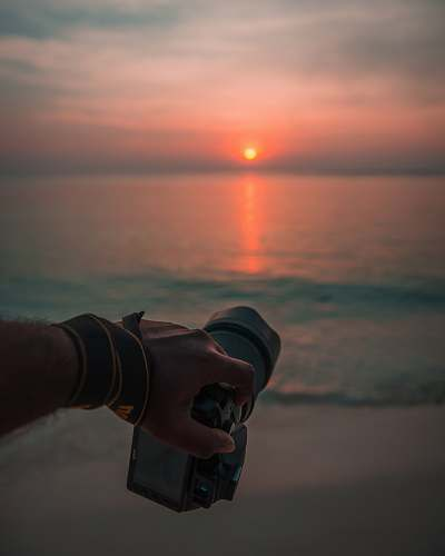nature person holding camera near sea during golden hour outdoors