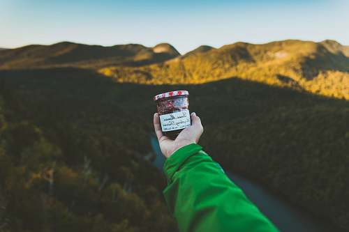 hiking person holding clear glass jar with cap near mountain jar