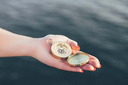 hands person holding gold-colored pocket watch compass