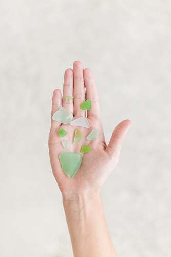glass person holding green shards sea