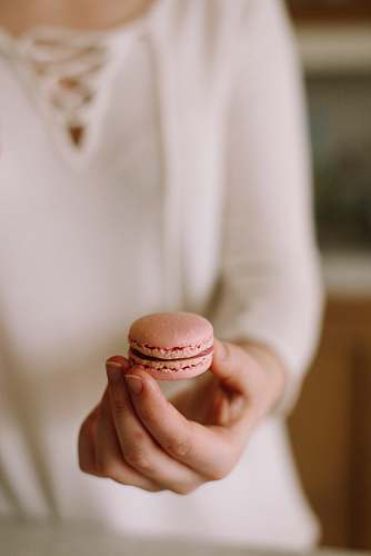 london person holding pink macaroon united kingdom