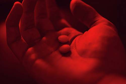 finger person holding two medicine pills red