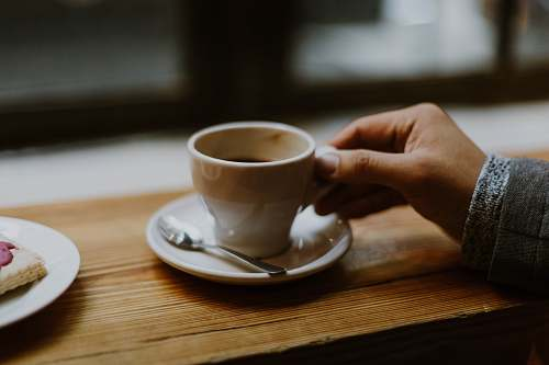 coffee person holding white ceramic tea cup cup