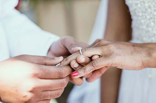 holding hands person putting ring on ring finger of woman wedding