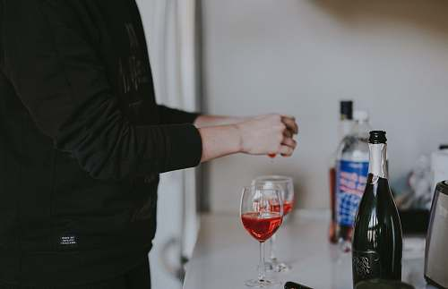 wrist person standing beside two wine glasses bottle
