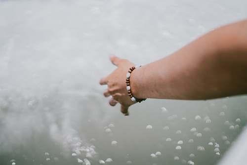 human person wearing beaded brown-and-white bracelet touching splashing water person