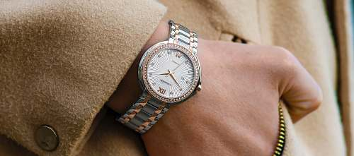 wristwatch person wearing round gold-colored analog watch with link band watch