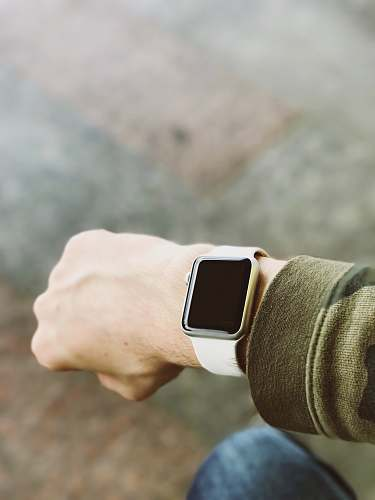 wrist person wearing silver platinum Apple Watch and white Sport Band apple watch