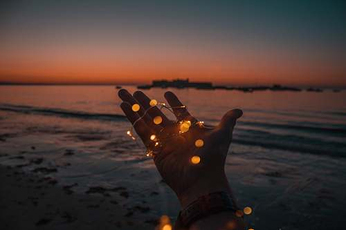 fairy lights person with string lights on left hand beach