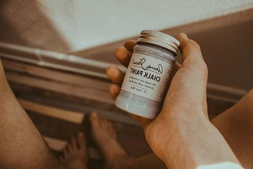 holding person's hand holding Chalk Paint bottle chalk paint