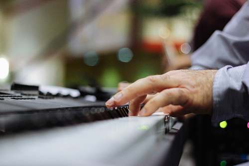 music selective focus of person playing piano jewelry