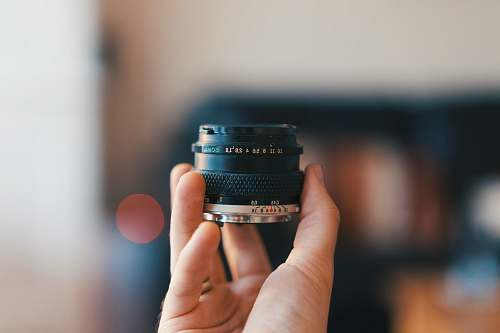 camera selective focus photography of person holding camera lens electronics
