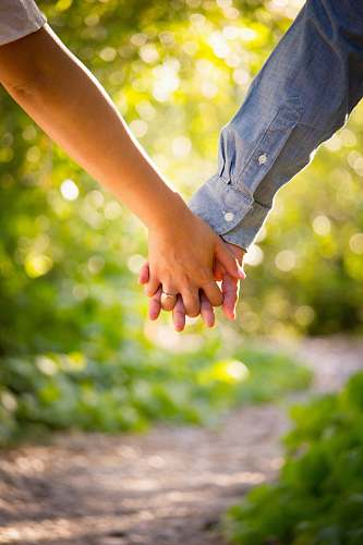 holding hands shallow focus photo of man and woman holding hands love