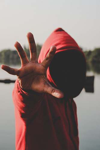 human shallow focus photography of person in red hooded jacket people