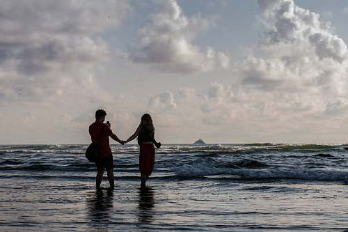 person silhouette of two people holding hands at seashore human