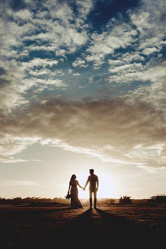 holding hands silhouette photo of man and woman under clear blue sky person