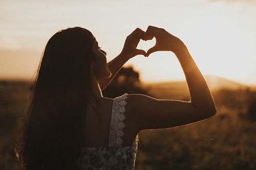 person woman forming heart with her both hands human
