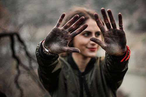 person woman showing her hands with black paint people