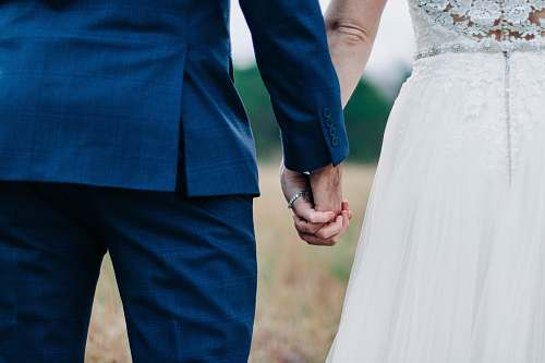 human woman wearing white wedding dress and man wearing blue suit holding hands during daytime holding hands