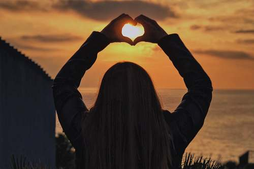 photo person woman with hands in heart shape at sunset human free for commercial use images