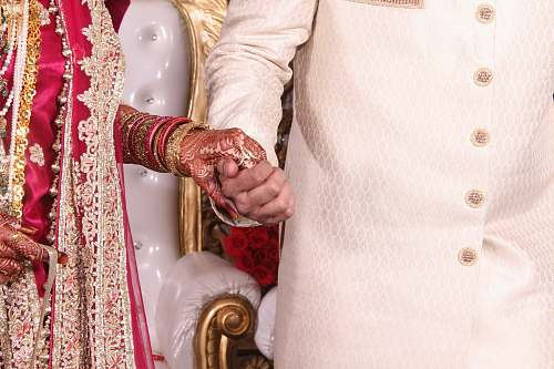 wedding Bride in red and gold dress holds hands with groom in India india