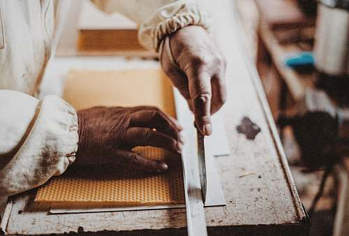 work person holding chisel while carving wood knife