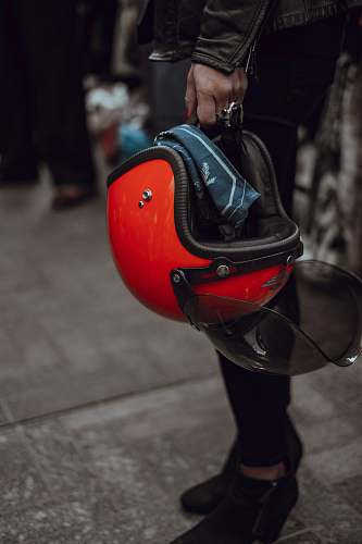 red person holding red half-face helme carrying helmet