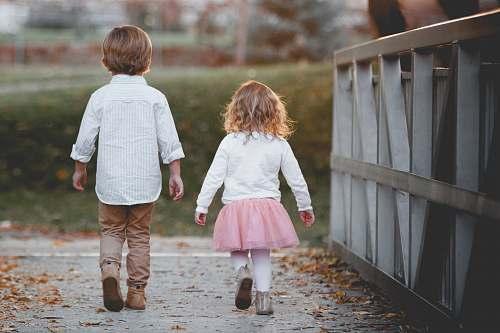 person boy beside girl walking near railing people