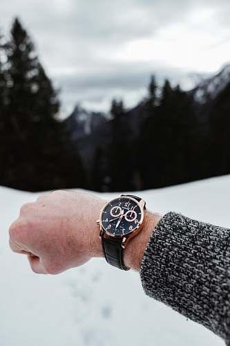 person chronograph watch reading 12:30 o'clock wrist