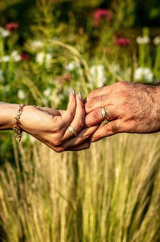 person holdings hands with gold-colored ring over flower garden hand