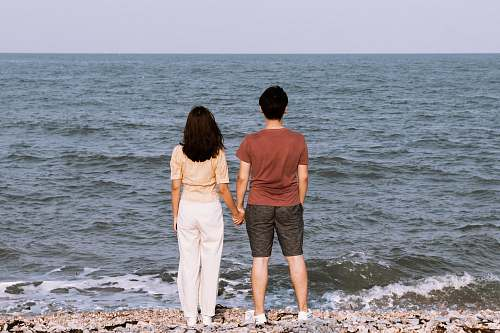 person man and woman standing infront of ocean water at daytime people