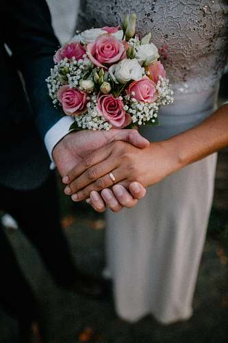 person man and woman standing while holding hands wedding