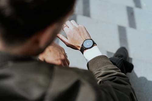 wristwatch man looking at watch on left wrist finger
