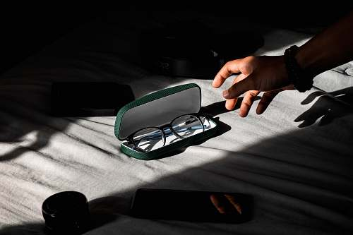 person person about to hold black-framed eyeglasses in case finger