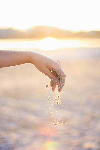 hand person dropping grains of sand holding hands