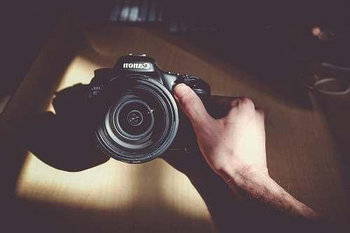 person person holding Canon DSLR camera people