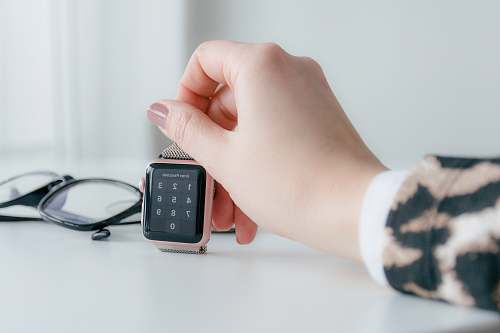 person person holding gold-colored smartwatch mobile phone