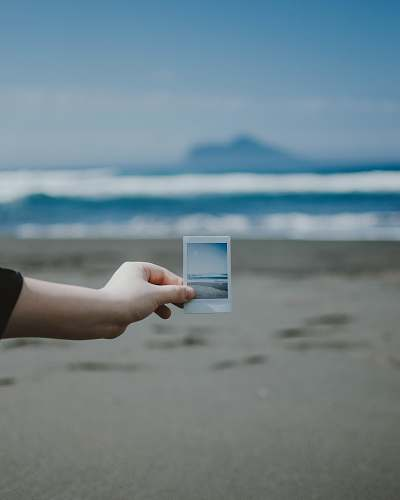 person person holds photo of ocean at the beach finger