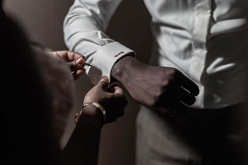 person person putting pin on another person's white dress shirt finger