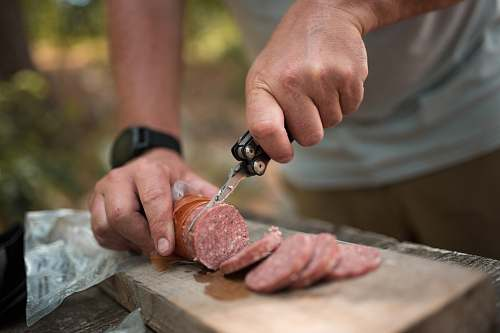 person person slicing sausage using butterfly knife finger