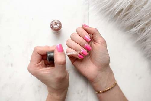 nail person spreading glittered nail polish on pink nails beauty