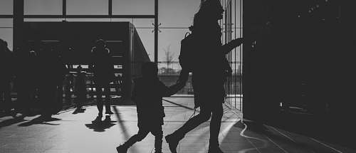 black-and-white silhouette of woman holding child grey