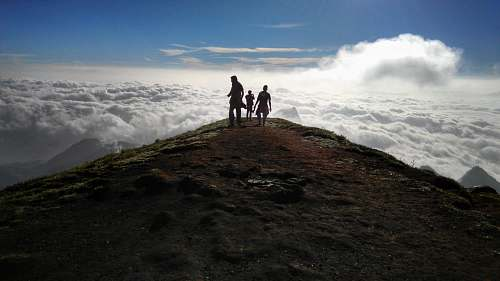 person three person on mountain peak with sea of clouds outdoors